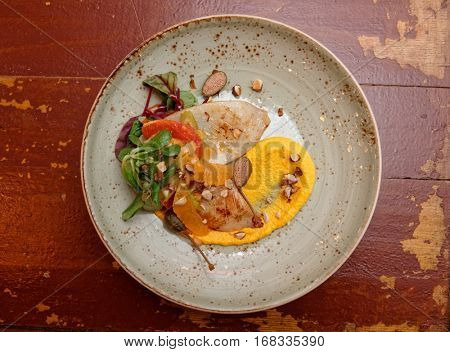Seafood starter with orange slices and pumpkin mash on old wooden table