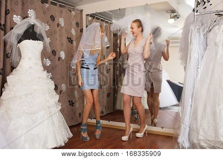 Two girlfriends - A Bride-To-Be and bridesmaid - having fun -Trying On A Wedding veils