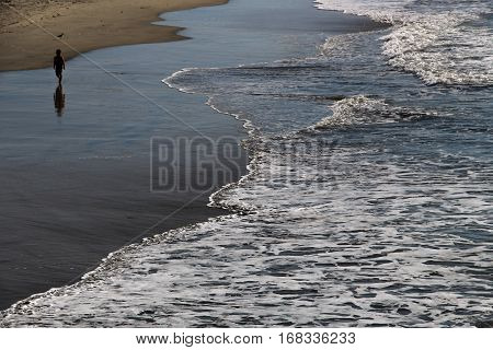 Silhouetted figure walking on wet beach with foamy waves encroaching