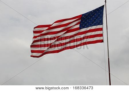 American flag blowing in wind against light gray sky