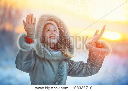 Young happy woman in warm winter clothing throwing up snow. Red sunset colors.