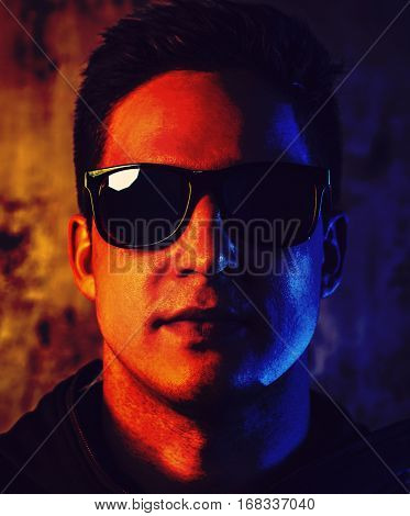 Young cool man in sunglasses closeup portrait. Very contrast and saturated red and blue colors dramatic style.