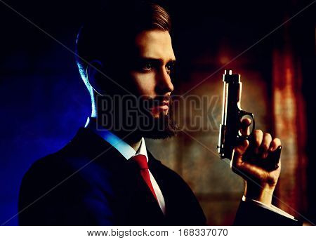 Danger man with gun looking aside portrait. Contrast dramatic red and blue colors
