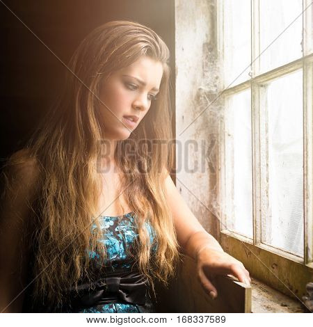 Sad young woman by window
