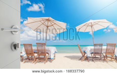 Opened White Door To Table Set And Umbrella On The Beach