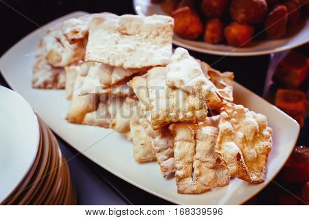 Plate with Russian sweet dough fried, called Brushwood. Plate with delicious pies close-up