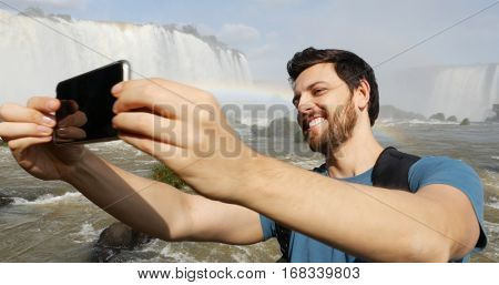 Tourist taking selfie photo in Iguazu Falls, Brazil
