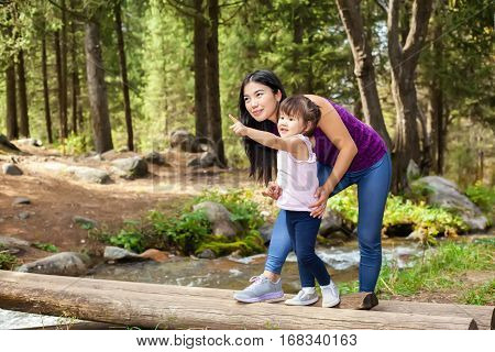 Asian Woman with her little daughter in the woods near the river standing on a log. posing smiling litle baby indicated hand