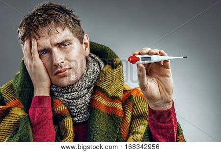 Sick man shows the temperature on the thermometer. Young man suffering cold and winter flu virus. Health care concept
