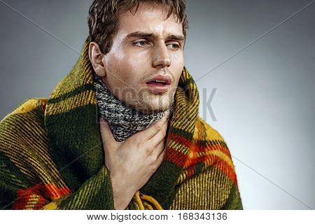 Unhappy man with sore throat. Sick man wrapped in blanket suffering fever and flu. Health care concept