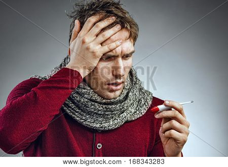Attractive man reading his temperature on a thermometer. Ill man suffering cold and winter flu virus. Health care concept