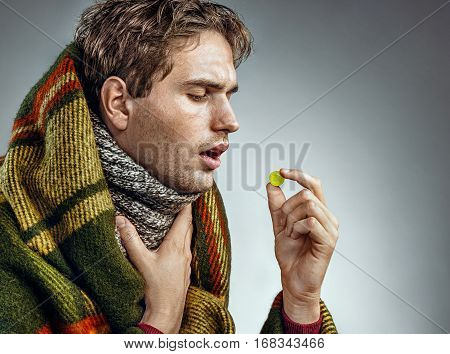 Ill man with open mouth take pills for throat. Man wrapped in blanket suffering from sore throat Health care concept