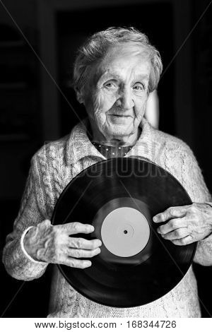 Elderly woman with vinyl lp disc in her hands. Black-and-white photo.
