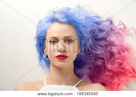 Trendy hairstyle concept. Young woman with colorful dyed hair on white wooden background poster