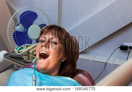 Girl patient during treatment at dentist office with saliva ejector.