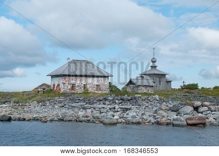 Ancient wooden church and an outbuilding on the shore of the White Sea. Religion architecture history