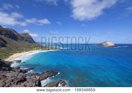 Wide angle rugged coastal seascape of Makapu'u Beach with Kaohikaipu and Rabbit Island surrounded by beautiful blue ocean under sunny sky in Oahu