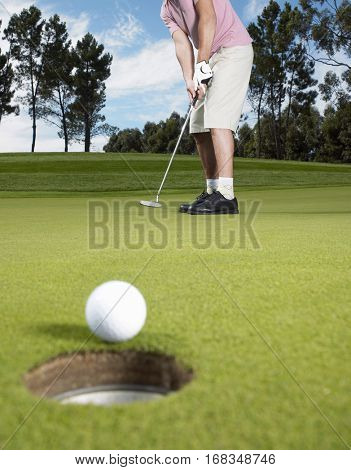 Full length of young male golfer putting ball on green