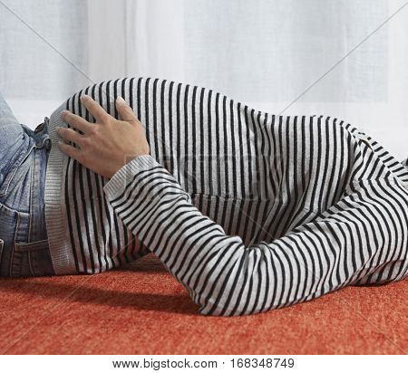 Side view portrait of a young pregnant woman lying on floor