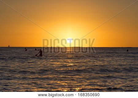 Silhouettes of surfers and paddle boarders on beautiful calm ocean as the setting sun colors the sky in brilliant orange hues at Waikiki Oahu