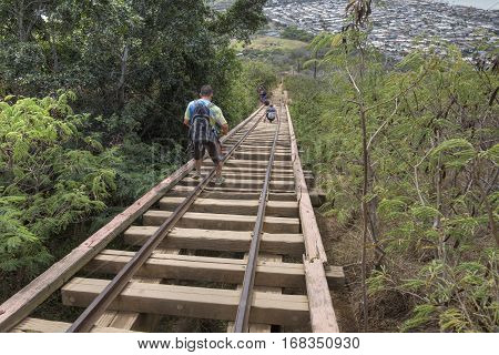 KOKO CRATER OAHU USA - JANUARY 20 2017: Hikers carefully maneuver down the old cart rail leading down from the summit of Koko Crater a popular day hike destination near Honolulu.