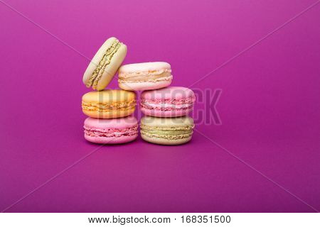 Sweet And Colorful French Macaroons Or Macarons Biscuits On Purple Background