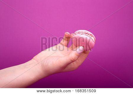 Woman's Hand Holding Pink Macaroon Or Macaron Dessert On Purple Background