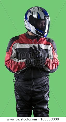 Male wearing protective leather and textile suit for racing race cars or motorcycles. The armor is worn in professional motor sports. The man is on a green screen or chroma key background.