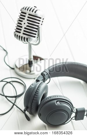 Headphones and microphone on white table.