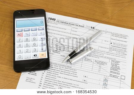 A shot of US Income Tax Return Form 1040 with a calculator on a smartphone.