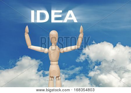 Wooden dummy puppet on sky background with word IDEA. Abstract conceptual image