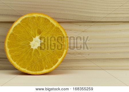 cut fresh juicy natural sour orange on wooden background