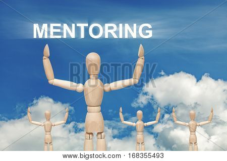 Wooden dummy puppet on sky background with word MENTORING. Abstract conceptual image