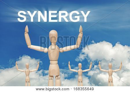 Wooden dummy puppet on sky background with word SYNERGY. Abstract conceptual image
