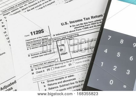 Close up shot of United States Internal Revenue Service (IRS) tax return form 1120S for small business also known as S-Corps next to a calculator.