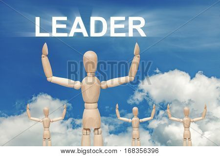 Wooden dummy puppet on sky background with word LEADER. Abstract conceptual image