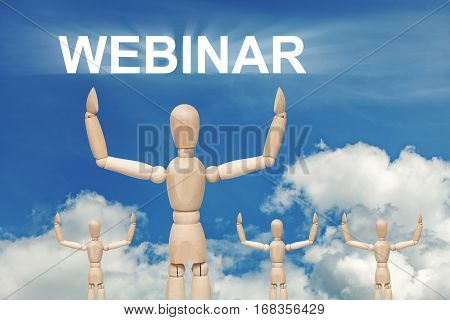Wooden dummy puppet on sky background with word WEBINAR. Abstract conceptual image