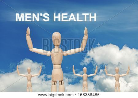 Wooden dummy puppet on sky background with words MEN'S HEALTH. Abstract conceptual image