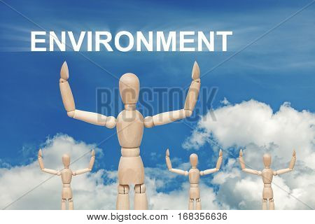 Wooden dummy puppet on sky background with word ENVIRONMENT. Abstract conceptual image