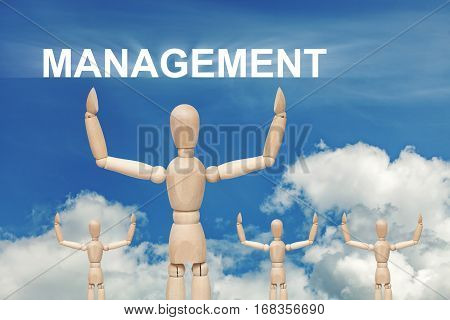 Wooden dummy puppet on sky background with word MANAGEMENT. Abstract conceptual image