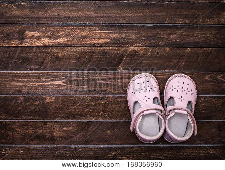 Little shoes on a dark wooden floor. Pair of baby girl shoes. Top view. Toned.