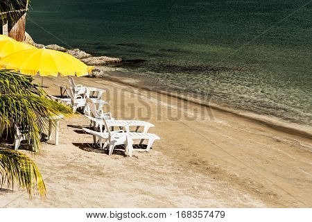 Yellow parasol and recliners on the beach in Subic bay Philippines