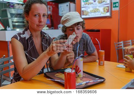 Mother and her son sitting in fast food cafe and drinking soda