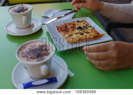 Two cappuccino and slice of pizza on plate on green table in cafe
