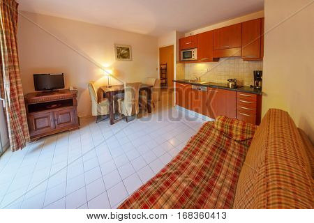 SAINT-TROPEZ, FRANCE - AUG 2, 2016: Interior of hotel room, view of kitchen and living room with television set
