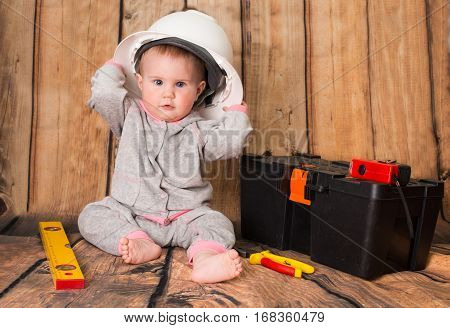 Funny cute baby in helmet playing with tools on wooden background.