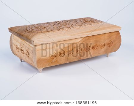 Picture of the carved wooden jewel-box for bijouterie on isolated white background. Carved pattern on a jewel box. Closed box made of light wood. Side view.