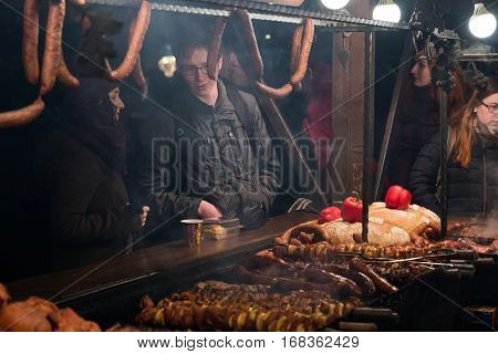 Krakow, Poland - December 19, 2016: People visit Christmas market at main square in old city and buy various traditional food
