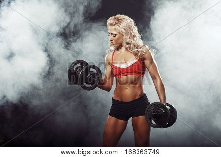 Photo Of Athletic Young Blondy Curl Girl Doing A Fitness Workout With Dumbbells On Smoke Background