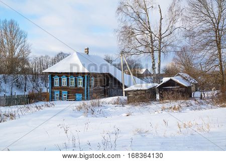 Winter rural landscape with a log house on a snowy street